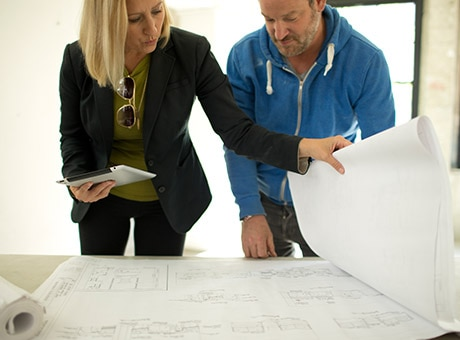 Owner of a growing business reviews floorplans for a new location