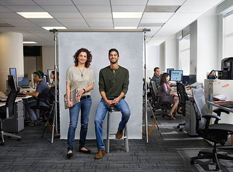 A pair of project managers pose while project workers work behind them
