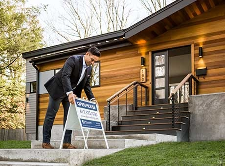 A real estate agent places an open house sign outside a recently closed down business