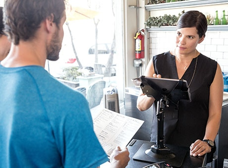 A restaurant cashier takes a patron order on a computer powered by QuickBooks software