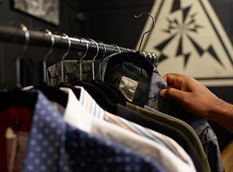 An employee adds new products to a retail clothing rack