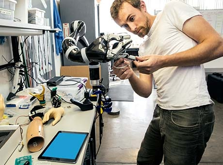 Employee at robotics manufacturer adjusts an arm based on collaborative input