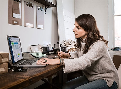 A small business owner reviews her company's financial statement on a laptop