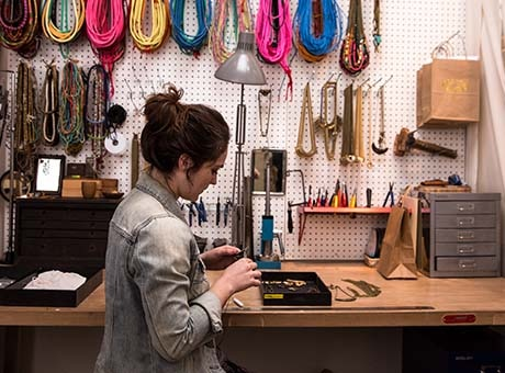 A woman creates craft products in her shop for sale on an online marketplace