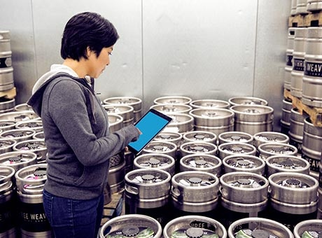 Worker reviews kegs for spoilage or damage
