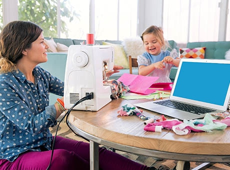 A worker runs a sewing machine with her daughter in a family friendly workplace