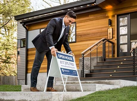 A real estate agent places an open house sign outside a property