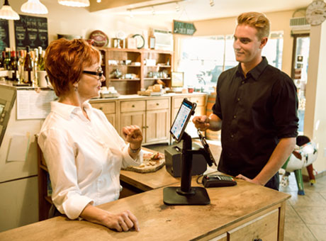 Side business owner using tablet with customer in retail store