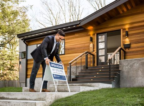 Real estate agent sets out open house sign in front of home for sale