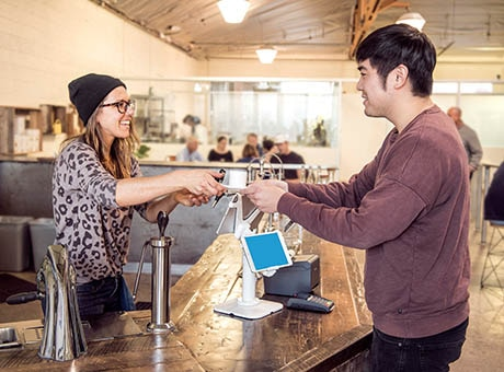 A coffee shop clerk helping cash flow by completing a cash sale