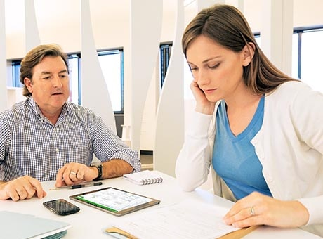 A small business owner reviews a disability insurance policy with an insurance agent