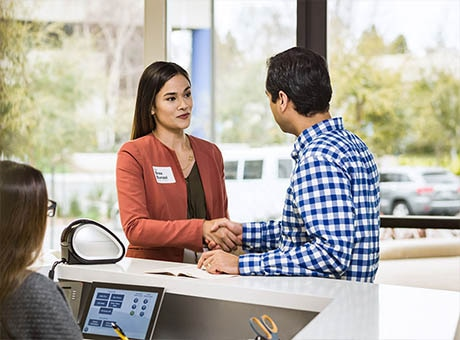 Professional woman introduces herself to man at office counter for marketing purposes