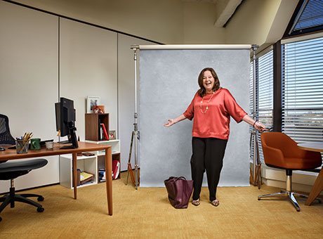 Woman in accounting office poses for photo while discussing operating leases with briefcase nearby
