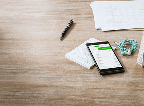 Smartphone on accounting office desk with financial analysis on the screen