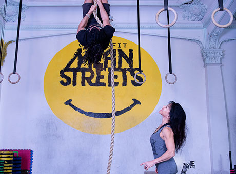 Aerial aerobics instructor gives a personalized lesson to a client after adjusting her business model