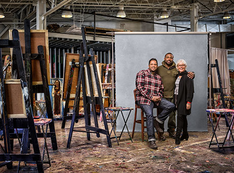 Nonprofit artists discuss tax implications while posing for photo near art easels