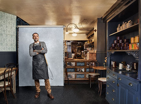 Small business owner in bakery discuss fiscal year projections while wearing an apron