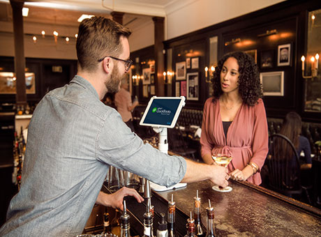 Sales professional at restaurant manages time while serving customer a beverage at bar