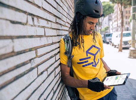Independent contractor with bicycle helmet views payroll processing on tablet
