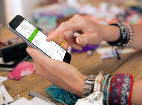 A business owner checking credit card payments received using Square at a craft show