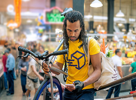 Business entrepreneur on bicycle evaluates tasks on mobile device