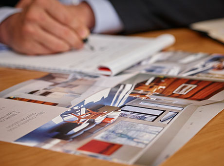 Real estate agent creates a client list on desk next to brochures