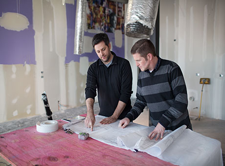 Two men viewing blueprints on job site discuss outsourcing business