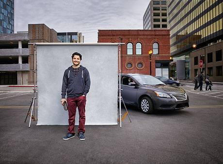 Driver discusses vehicle charging stations while standing near parked car
