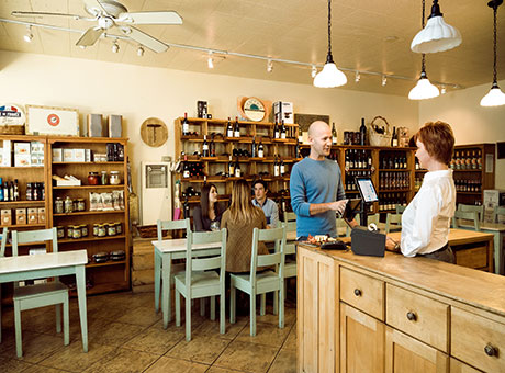 Small business owner greets customer in cheese gallery near racks of wine