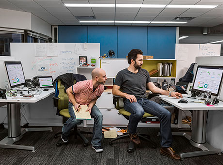 Two developers in office cubicle perform beta testing on laptop
