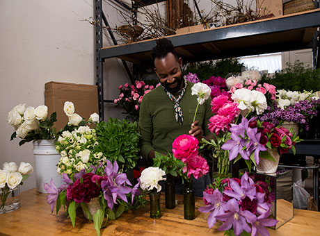 Man in floral shop processing inventory on counter with vases and flowers