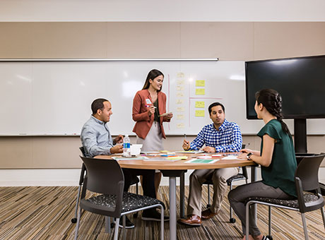 Business professionals at table discuss key performance indicators near white board