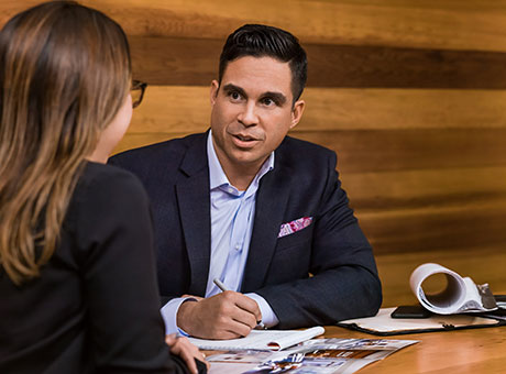 Hiring manager meets with female in office while writing on notepad on table