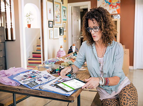 Freelance designer reviews continuing education opportunities on tablet in home office