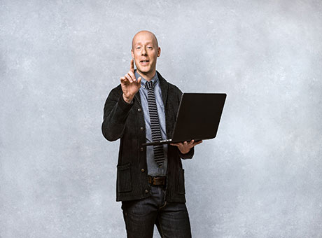 Accountant discusses ticket sales while holding laptop in front of grey backdrop