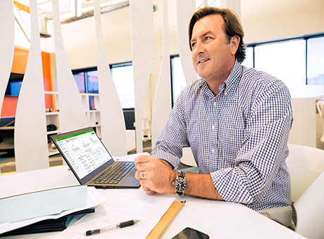 Financial advisor sitting at office desk evaluates sales techniques with laptop on table