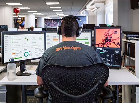 Developer works on custom email domain at office desk with two computer screens