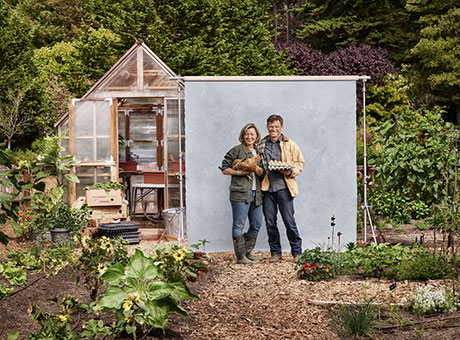 Rural business owners pose for photo in garden holding an animal and eggs
