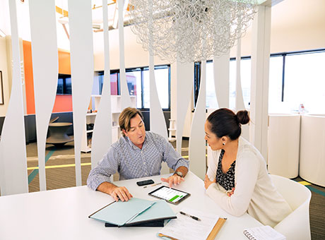 Accountant and female client in office discussing business acquisitions