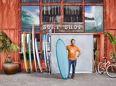 Surf shop owner poses for photo outside of second business holding surf board