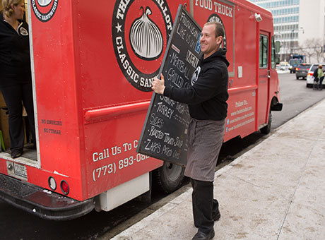 Food truck employee hangs promotional sign near city street