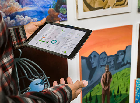 Artist in gallery holds tablet displaying emergency funds available