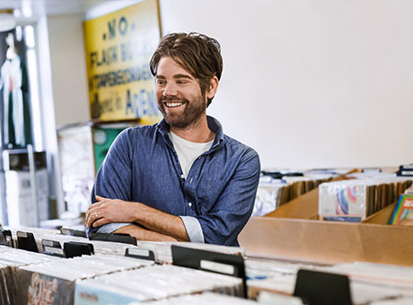 Musician in retail store discusses marketing strategies near stacks of records