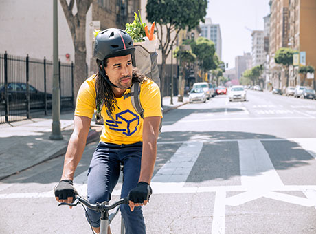 Bike repair shop owner rides bicycle on city street wearing helmet