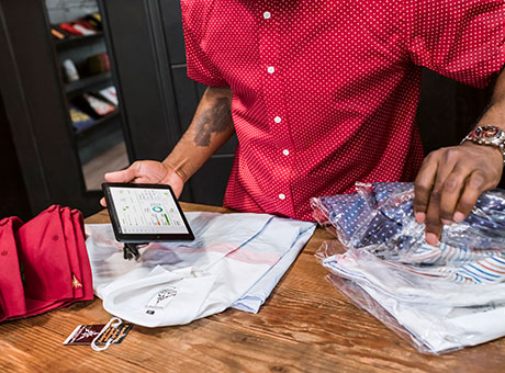 Small business owner sorts through clothing inventory while holding tablet