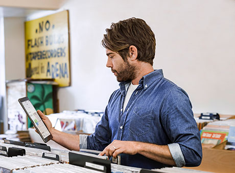 Man holding tablet in record retail store views tax return while sorting merchandise
