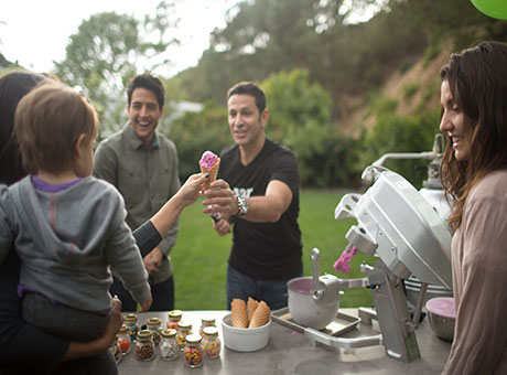 Ice cream vendor hands cone to woman and child at outdoor company retreat