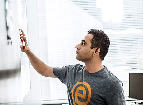 Developer evaluates multiple share classes near whiteboard in office