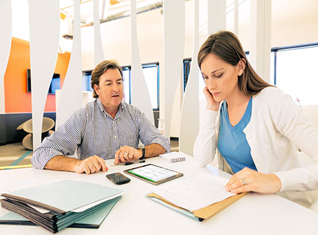 Man and woman in consulting office evaluate market research with tablet and financial paperwork on table