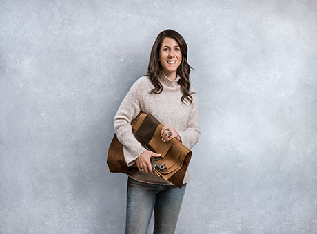 Woman from online store displays bag while posing for photo to upsell customers